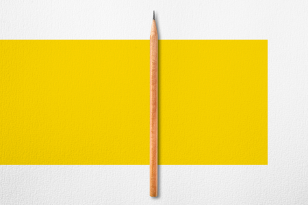 Minimalist template with copy space by top view close up photo of wooden pencil put in the center of texture white paper and combine with yellow rectangle.Flash light made pencil have smooth shadow.