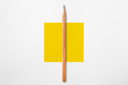 Minimalist template with copy space by top view close up photo of wooden pencil put in the center of texture white paper and combine with yellow square. Flash light made pencil have smooth shadow.
