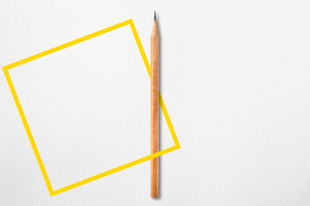 Template with copy space by top view close up photo of wooden pencil put in the center of texture white paper and combine with square yellow line. Flash light made pencil have smooth shadow.