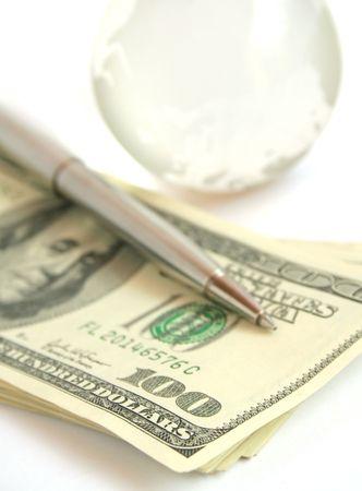 International Banking - Hundred dollar bills, pen and a glass globe photo