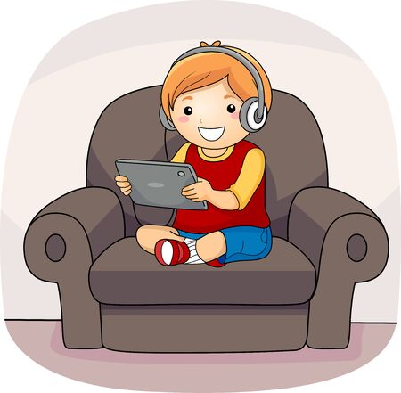 Kid Boy Using a Tablet Computer and Wearing Headphones While Sitting on a Couch Banco de Imagens