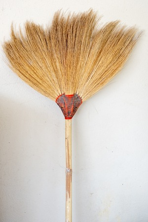 broom or broom head to sweeping the dust or cleaning floor on white plain wall.