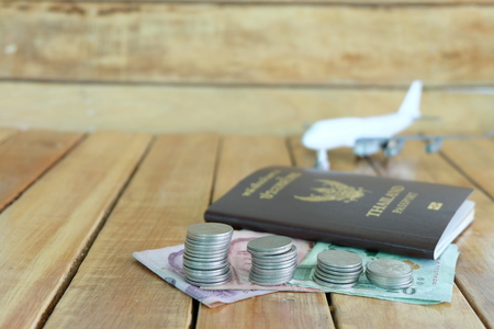 Money saving concept for vacation with coins stack, passport, and aircraft toy on the wooden backgrounds