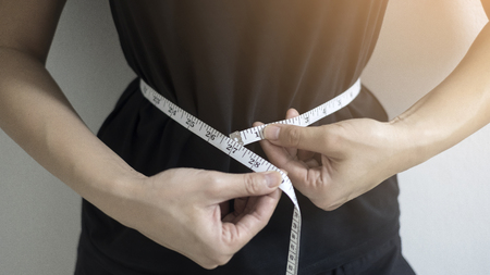 Diet concept close up women measuring waist circumference. Banco de Imagens