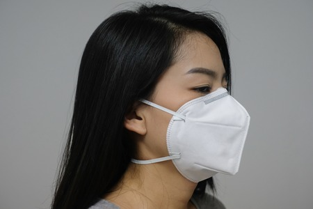 Woman wearing face mask of N95 because of air pollution in the city have particulate matters or PM 2.5.