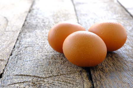 Chicken eggs on old wooden background