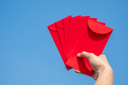Happy Chinese new year, Hand holding red envelope or called Angpao on sky background. 版權商用圖片
