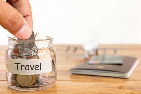 Travel budget concept. Travel money savings concept. Collecting money in the money jar for travel. Money jar with coins, aircraft toy, and passport.