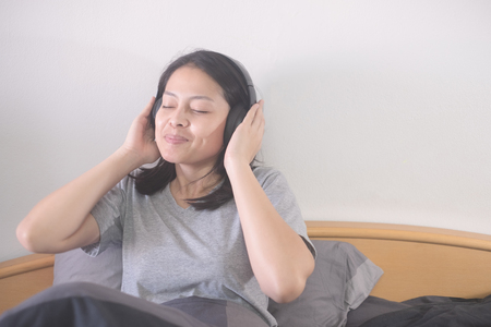 beautiful Asian woman listening music with headphone relaxing on the bed