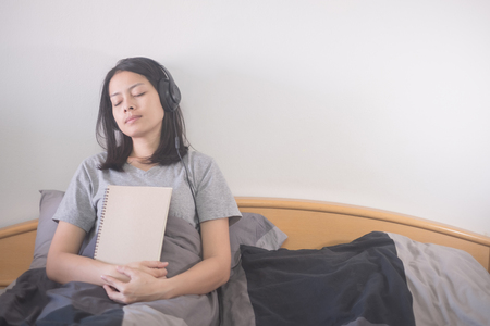 beautiful Asian woman listening music with headphone and reading book relaxing on the bed 免版税图像