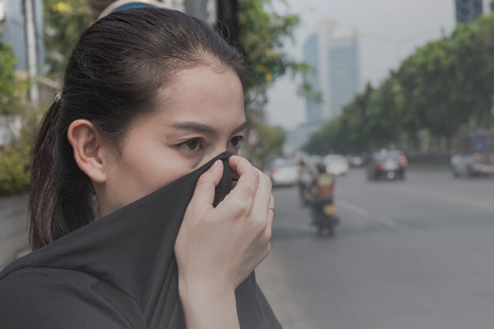 woman closes her nose with hand because of bad traffic pollution 免版税图像