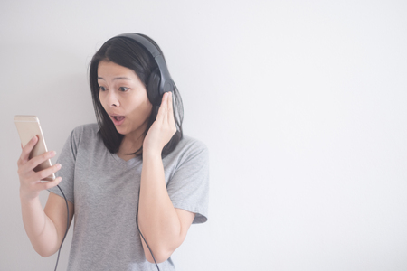 beautiful Asian woman listening music with headphone and smartphone isolated on a white background with copy space
