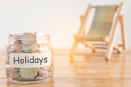 Holidays budget concept. Holidays money savings concept. Collecting money in the money jar for Holidays. Money jar with coins and beach seat on wooden background