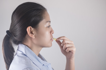 Healthy eating and diet nutrition concepts. vitamin and supplement. beautiful Asian young woman holding yellow fish oil pill. female hand putting omega-3 capsule in mouth.