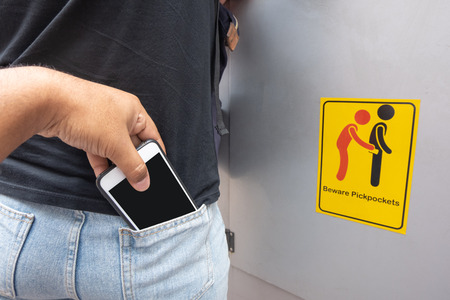 Thief stealing mobile phone from back pocket of a woman with beware pickpockets sign symbol background
