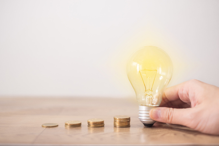 new idea concept with coins stack, young women hand holding light bulb with new knowledge on wooden backgrounds and new idea concept save power to save the earth
