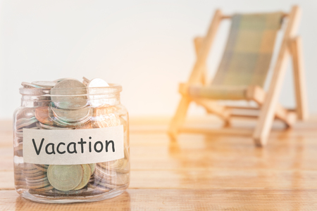 Vacation budget concept. Holidays money savings concept. Collecting money in the money jar for Vacation. Money jar with coins and beach seat on wooden background