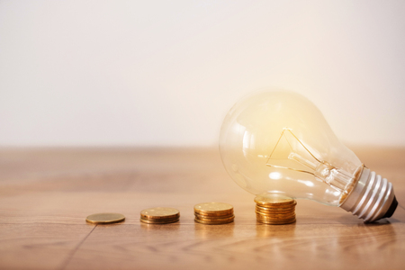 save power to save the earth concept with coins stack, light bulb with new knowledge on wooden backgrounds and new idea concept 免版税图像