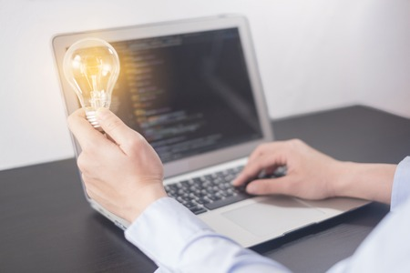 Young woman programmer hand holding light bulb, woman hands coding and programming on screen laptop, new ideas with innovation and creativity concept