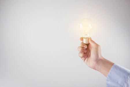 hand holding light bulb, new ideas for discovery inspiration