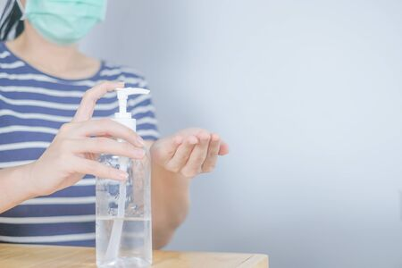 Closeup Asian woman wearing protective mask using hand sanitizer by pumping alcohol gel. Cleaning her hands with sanitizer gel. in quarantine for coronavirus wearing protective mask Hygiene concept.