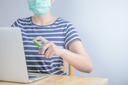 Asian woman wearing protective mask using spray alcohol sanitizer cleaning a computer, to prevent the virus and bacterias, woman in quarantine for coronavirus.Cleaning her computer with spray alcohol