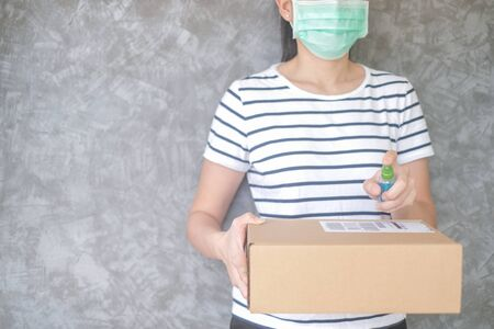 woman wearing protective mask using spray alcohol sanitizer cleaning parcel post to prevent virus and bacterias from Postal sender she protects herself and her family from virus woman giving package