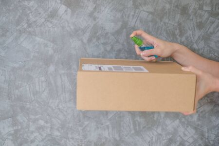 woman using spray alcohol sanitizer cleaning parcel post to prevent virus and bacterias from Postal sender she protects herself and her family from virus woman giving package 免版税图像