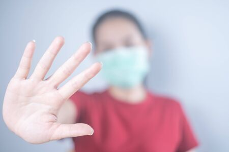 Asian woman wearing a hygiene protective mask to protect COVID-19 and Show hand, don't come in. Self-isolate or Self-quarantine for protects against the spread of virus disease