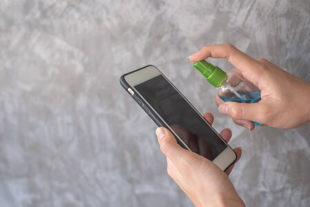 Closeup woman hands using spray alcohol sanitizer cleaning screen smartphone, to prevent the virus and bacterias. Clean smartphone. measures against Covid-19. Hygiene concept.Cleaning concept.