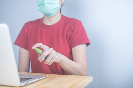 Asian woman wears protective mask using spray alcohol sanitizer cleaning a computer, to prevent the virus and bacterias. woman in quarantine for coronavirus.Cleaning her computer with spray alcohol