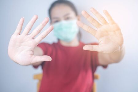 Asian woman wears hygiene protective mask to protect COVID-19. Show hand, don't come in. Self-isolate or Self-quarantine for protects against the spread of virus disease 免版税图像