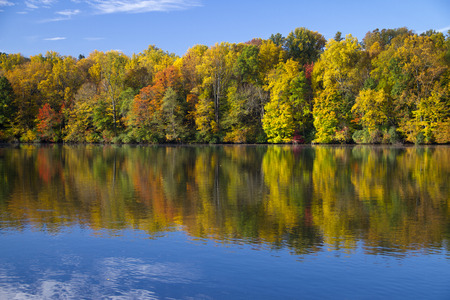 Colored trees on fall reflected by lake Stock Photo