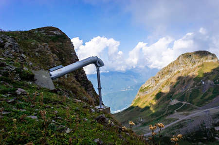 Avalanche exploder in the Caucasus Mountains, Aibga ridge against the background of a cloudy sky, summer landscape, Avalanche control system
