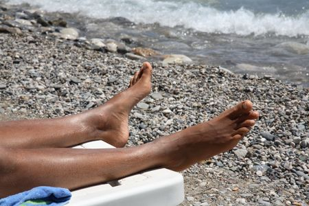 suntanned: Suntanned female feet on a white beach plank bed Stock Photo
