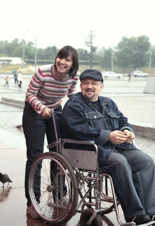 man in an invalid carriage and his wife on walk Stock Photo - 5072490