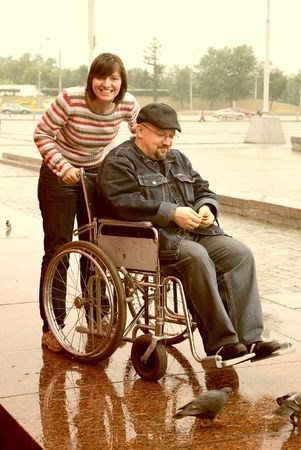 man in an invalid carriage and his wife on walk Stock Photo - 5072493