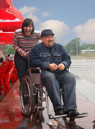 man in an invalid carriage and his wife on walk Stock Photo