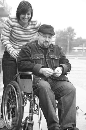 invalidity: man in an invalid carriage and his wife on walk Stock Photo
