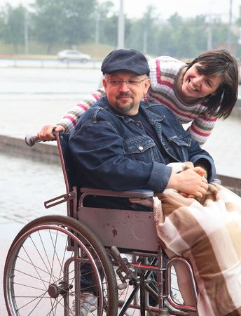 handicapped person: man in an invalid carriage and his wife on walk Stock Photo