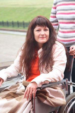 invalidity: young woman on walk in an invalid carriage