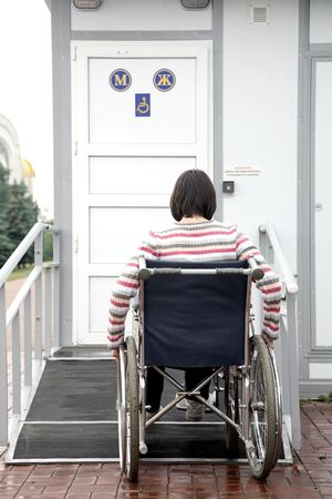 physical impairment: woman in an invalid carriage tries to move down in a toilet for invalids