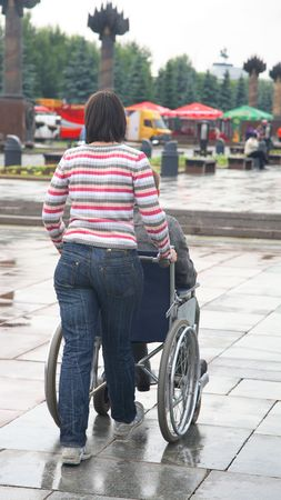 young woman carries an invalid carriage Stock Photo - 5128776