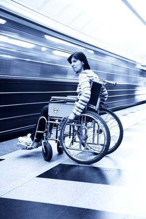 wheelchair access: woman in an invalid carriage in the underground