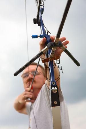 man  shooting to archery target. photo