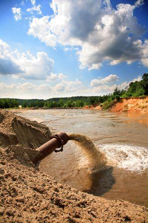 abwasser: Abwasser flie�t aus einem Rohr in den Fluss Lizenzfreie Bilder