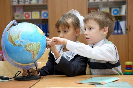 Pupils at a geography lesson examine the globe photo