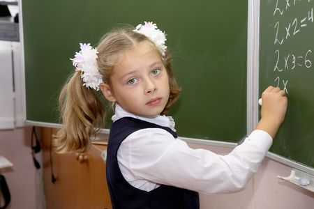 grade school age: schoolgirl of an elementary grade answers at a board Stock Photo