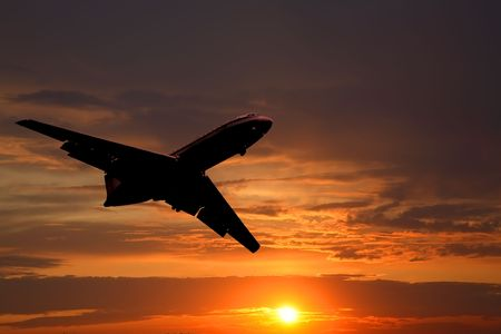 Silhouette of the big plane on a sunset background photo