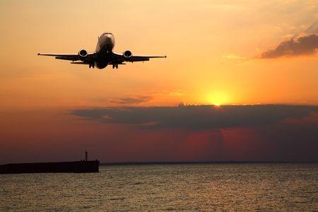 大きな飛行機、夕日を背景にシルエット 写真素材